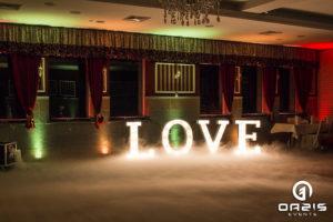 Świecący napis LOVE na tle dekoracji światłem i ciężkiego dymu.