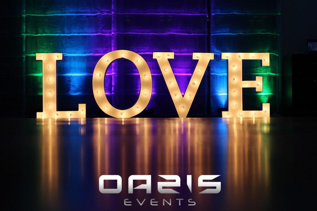 Napis LOVE okrągłe O na tle dekoracji światłem