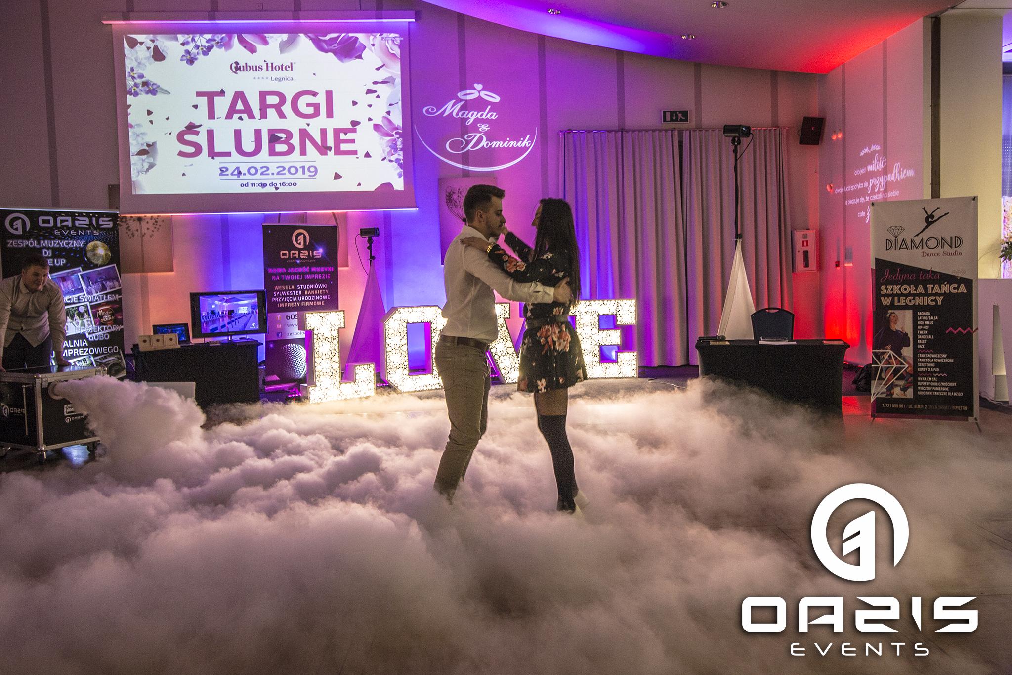 pierwszy taniec pary młodej na tle napisu love, cieżki dym