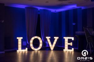Napis LOVE na tle dekoracji światłem